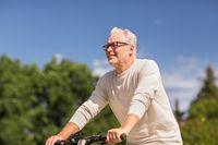 happy senior man riding bicycle at summer park