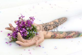 Girl's hands with tattoos and flowers