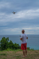 Man with drone camera taking photos of beautiful sea