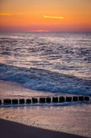 Old wooden breakwaters on the beach at sunset