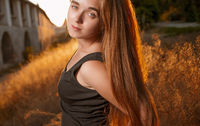 Young woman n calm state of mind with long blond hair backlit by sun selective focus toned image, sun flares