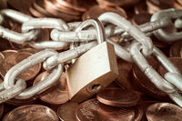 Pile of coins and a padlock with chain
