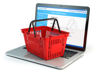 Online shopping e-commerce concept. Shopping basket on laptop keyboard isolated on white background.