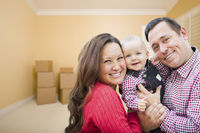 Young Family In Room With Moving Boxes