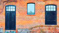 old red brick barn with wooden doors