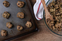 Top view of a baking sheet with raw cookie dough for making Chocolate Chip Cookies, with a bowl of d