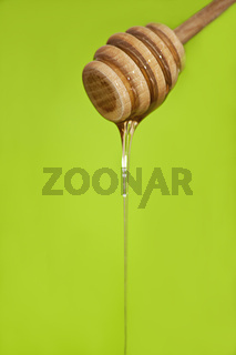 honey dripping from wooden honey spoon on green background