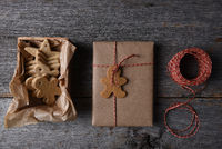 Top view of Christmas Presents with a box of Holiday Shaped Cookies on a rustic wood background.