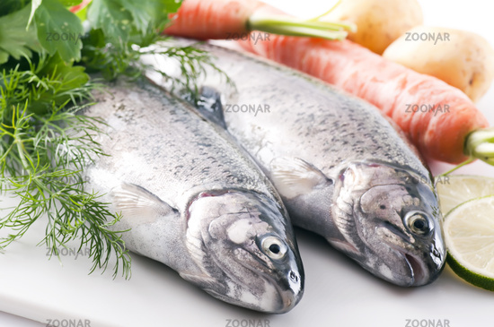 Two fresh rainbow trout with potatoes, vegetables and herbs as closeup on white background