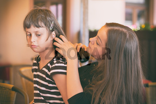 The girl combs her hair to her friend