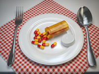Pils in the plate with fork and spoon. Pharmacy diet nutrition concept.