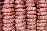 Rings of smoked pork sausage lie on the counter of a street vendor.