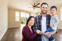Mixed Race Chinese and Caucasian Parents and Child Inside Empty Room of New House.