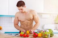 Junger Mann Bodybuilder kochen Essen Gemüse Mittagessen Internet Tablet Textfreiraum gesunde Ernährung