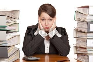 frustrierte überlastete Frau im Büro zwischen Ordnerstapel
