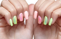 Female hands with woman's professional natursl pink and green nails manicure on white