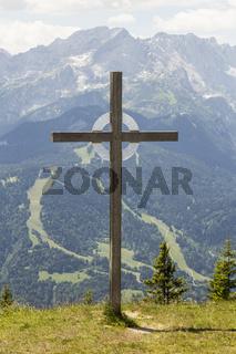 Ein Gipfelkreuz, im Hintergrund die Alpspitze bei Garmisch-Partenkirchen.