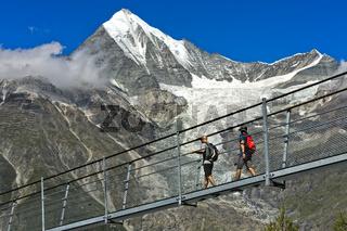 Wanderer im Abstieg auf der Charles Kuonen Hängebrücke vor dem Weisshorn Gipfel, Randa, Schweiz