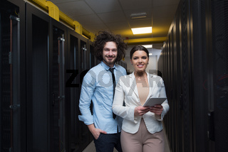 engineer showing working data center server room to female chief