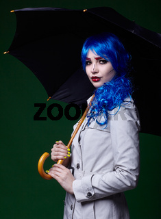 Portrait of young woman in comic  pop art make-up style. Female with umbrella on dark background