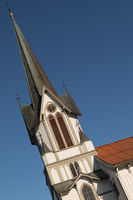 Tilted image of the tower of Bamble Church, a large wooden church. Winter, snow, sunshine and blue sky. Vertical image.