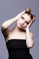 Young teen female beauty portrait with day makeup and bun hair style