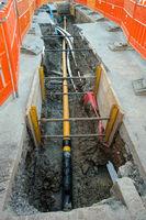 Offene Baustelle auf einer Straße mit Rohren und Kabel