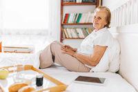 Happy elderly woman having breakfast in bed whilst using her tablet