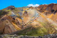 Travel to Iceland in the July. Multi-colored mountains from mineral rhyolite are lit with sun.  Summer volcanic tundra