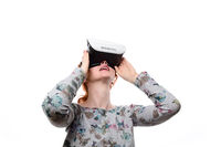 Beautiful girl getting experience using VR-headset glasses of virtual reality  and feeling surprise