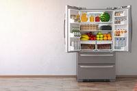 Open fridge  refrigerator full of food in the empty kitchen interior.