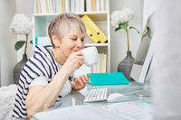 Ältere Geschäftsfrau trinkt eine Tasse Kaffee