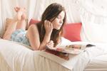 Junges Mädchen liegt mit Zeitschrift im Bett
