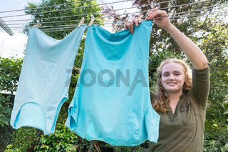 Young dutch woman hanging laundry at clothesline