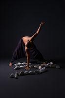 Man doing yoga white stones on the floor
