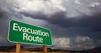 Evacuation Route Green Road Sign and Stormy Clouds