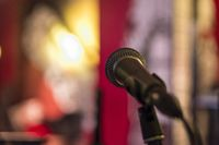 Closeup of a microphone in front of blurred background