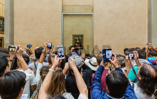 PARIS, FRANCE - August 18, 2017: Visitors take photo of Mona Lisa at the Louvre Museum