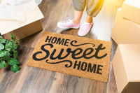 Woman in Pink Shoes and Sweats Standing Near Home Sweet Home Welcome Mat, Boxes and Plant