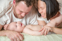 Mixed Race Chinese and Caucasian Baby Boy Laying In Bed with His Parents