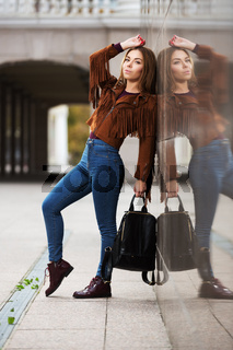 Young fashion woman in leather jacket with handbag on city street