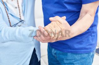 Zwei Senioren halten sich an den Händen