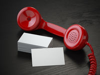 Mockup of  blank business cards and  red retro phone receiver  on  the black wooden desk background.