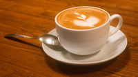 Hot cappuchino coffee cup on brown wooden table angle cloeup view