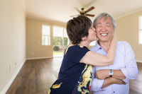 Happy Senior Chinese Couple Kissing Inside Empty Room Of New House.