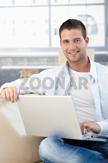 Handsome man with laptop smiling on sofa