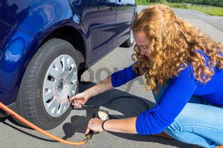 Girl checking air pressure of car tire