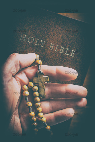Rosary beads in hand.