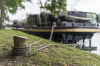 A moored at a wooden bollard barge on the canal bank