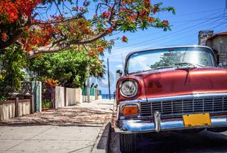 HDR - Roter amerikanischer Cabriolet Oldtimer parkt unter blauem Himmel in der Seitengasse in Varade